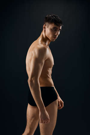 handsome athletic man with muscular body in dark panties