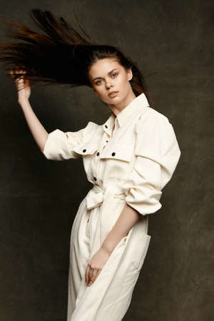 portrait of a woman in a white jumpsuit on a dark background suit posing model