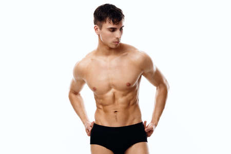 handsome man with a pumped-up torso holding his hands on his belt on isolated background