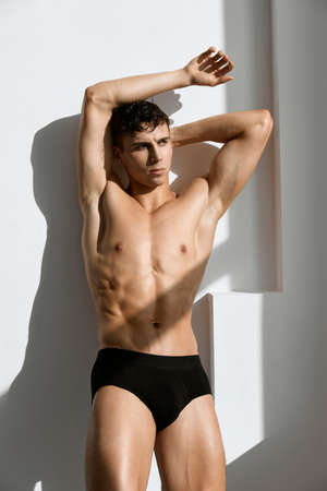 handsome man with muscular body in black panties posing