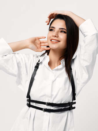 woman in white shirt with black suspenders holds her hands behind her head