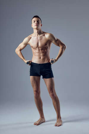 sporty man holding hands on the belt in black shorts inflated body exercise fitness Фото со стока