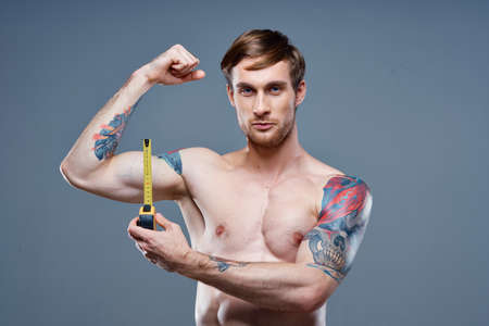 tattooed man muscular bodybuilder Fitness gray background Foto de archivo