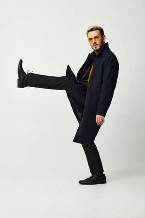 fashionable man in a coat lifted his leg up and glasses on his face side view