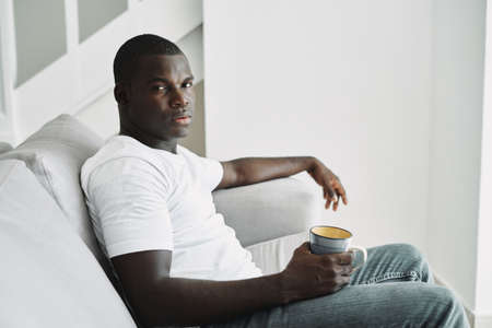man of african appearance sit on sofa rest interior