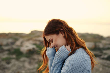 cheerful woman in a blue sweater outdoors sunset travel vacation