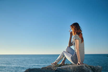 Woman hiker on a rock near the sea sunset blue sky and transparent water model
