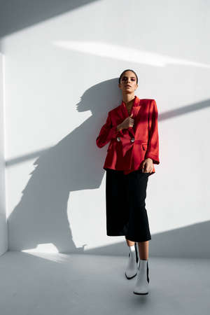 a woman in a red jacket and fashionable trousers leaned against the wall