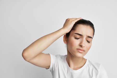 woman with headache dissatisfaction health problems medicine light background