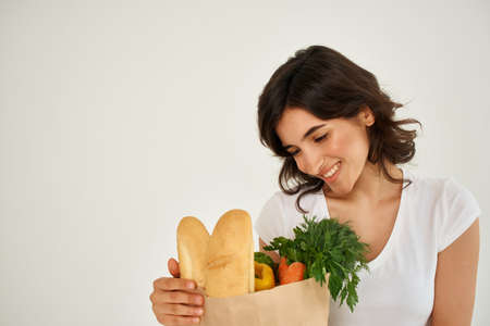 cheerful woman in a white t-shirt package with groceries from the supermarket health Stock Photo