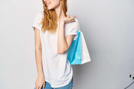 woman in white t-shirt with packages in hands shopping lifestyle entertainment