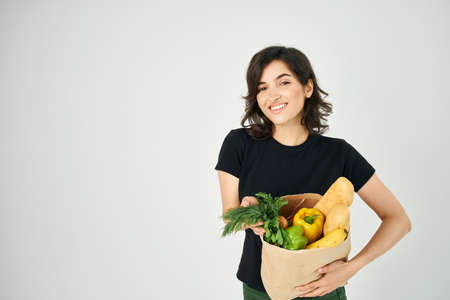 cheerful brunette in a black t-shirt package with groceries supermarket shopping