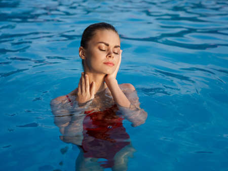 pretty woman with closed eyes glamor and luxury pool red swimsuit