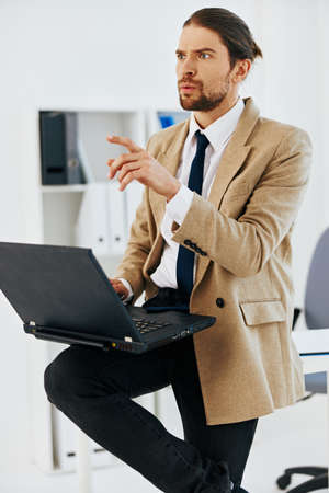 man in beige jacket in the office with a laptop executive