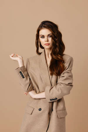 attractive woman model coat gesturing with hands on beige background Copy Space