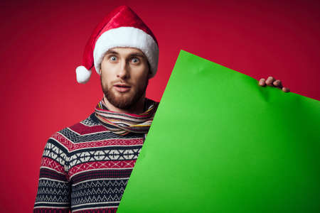 emotional man in a santa hat holding a banner holiday isolated background Standard-Bild