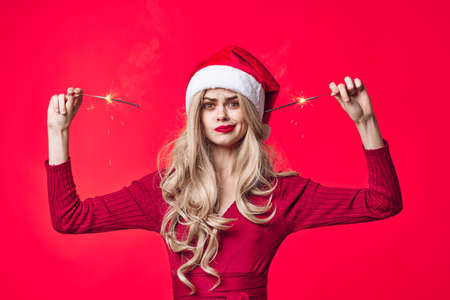 pretty woman in santa hat holiday christmas emotion sparklers Standard-Bild