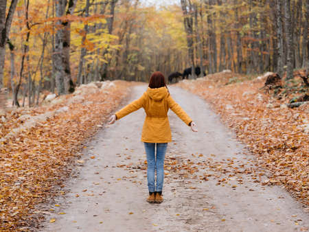 woman in a yellow jacket walks in the autumn forest fresh air