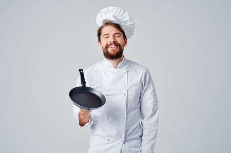 a man in a chefs uniform pan cooking kitchen Professional