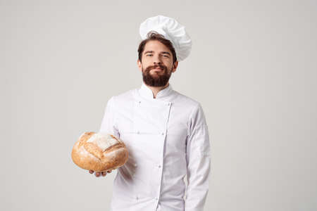 bearded man chef with bread in hand light background