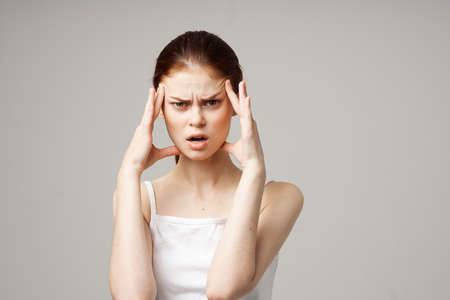 woman in white t-shirt headache health problems stress isolated background