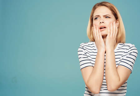 woman holding her head emotions displeasure upset blue background