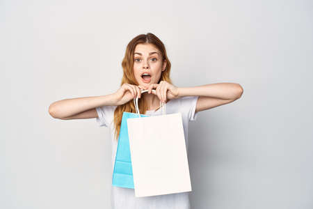 woman in white t-shirt with packages in hands shopping shop