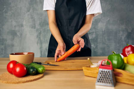 Woman in black apron lunch at home vegetarian food cutting board Banque d'images