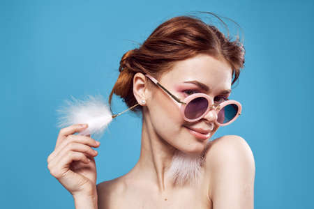 woman with fluffy earrings nude shoulders makeup clear skin