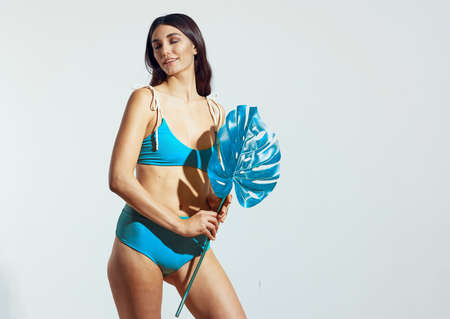 woman in blue swimsuit palm leaf beach summer home travel Banque d'images