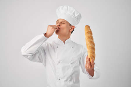 a man in chefs clothes with a baguette in the hands of a gourmet restaurants