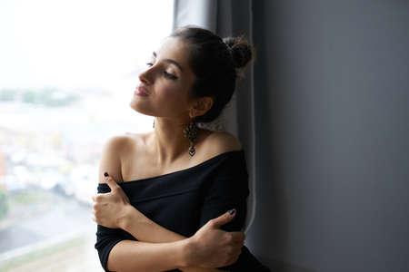 brunette near window posing attractive look earrings elegant style Banque d'images
