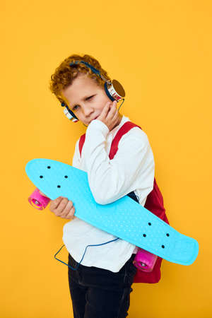 Boy carry skateboard and headphones on yellow background.