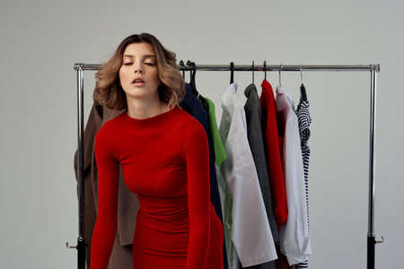 beautiful woman in a red dress stand near the wardrobe. Standard-Bild