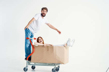 Man stand on trolley and woman inside the box.