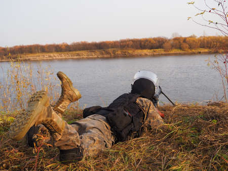 Machine gunner resting on the river Bank