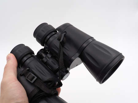 A man's hand holds a black tourist binoculars on a light background