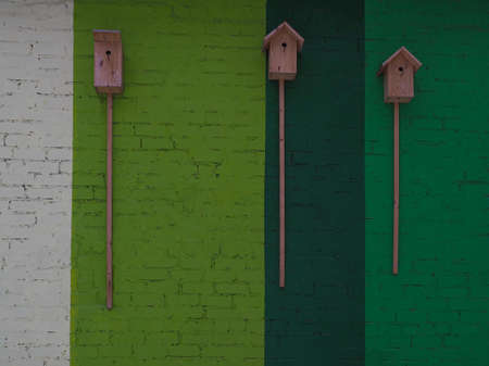 Birdhouses on a textured background of a multi-colored painted brick wall.