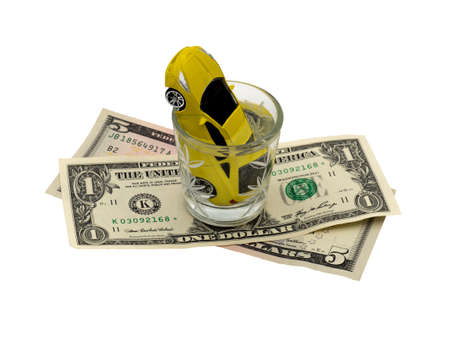 A yellow car is drowning in a glass of alcohol on dollar bills. Mac-up. Social advertising. Concept of drunk driving, car accident, financial expenses for the car.