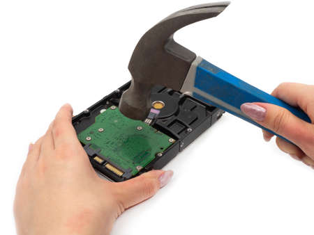 A woman's hand with a hammer smashes an old hard drive. The concept of anonymity and computer security, data deletion. Repair and upgrade to modern SSD (solid-state drive)