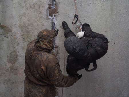 Training in military, assault and police mountaineering. Male instructor teaches a man in camouflage to climb down a wall on a rope. Special forces learning at the training ground. Photo without face.