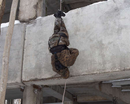 A man, a military (assault) climber descends head down (feet up) on a rope without insurance on the wall of a building. An employee of a special unit in camouflage at the training ground.