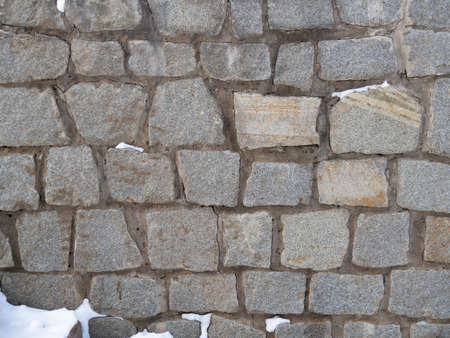 The texture of a rough medieval wall made of uneven cobblestones. The paving stone pattern. Stone old background covered with snow in winter.