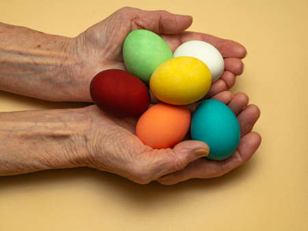 An old, elderly woman holds or gives, holds out multicolored, colored boiled chicken eggs in her wrinkled hands. Traditional elements of a happy Orthodox or Catholic Easter.