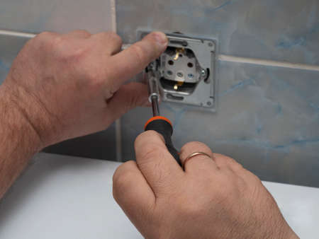 Economic husband, electrician, repairs, installs a outlet in bathroom. Man hand of master with wedding ring twists socket with screwdriver close-up against the background of wall ceramic tiles.
