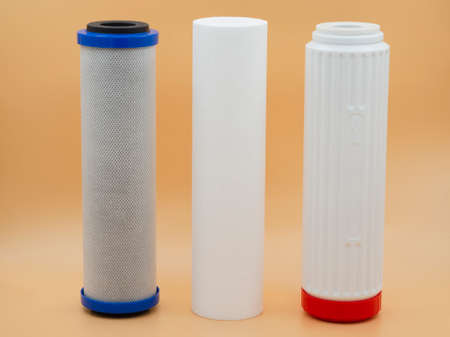 Three clean, new filter cartridge purifiers for running water on a gold fortune background. The concept of pre-cleaning, water softening, deep sorption cleaning.