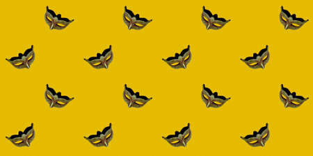 Classic Venetian theatrical mask isolated on a yellow background. Seamless texture of a repeating pattern. Wallpaper design concept.