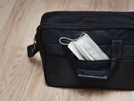 Black men's laptop bag with a medical mask in an open pocket on the background of a wooden floor or table. The concept of banning work without complying with measures against coronavirus. Stockfoto