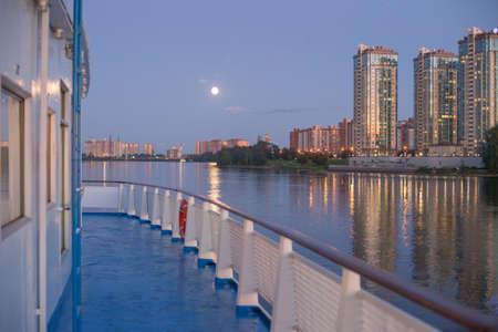 Het schip gaat langs de rivier de Neva. Zonsondergang. Maan.