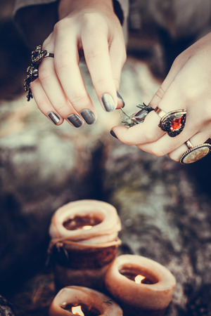 witchery: Girls hands putting a spell over the candles